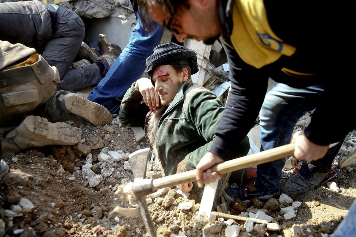 A rescuer works to free a man buried in debris at a damaged site after an airstrike in the Saqba area, in the eastern Damascus suburb of Ghouta, Syria, on Jan 9, 2018.