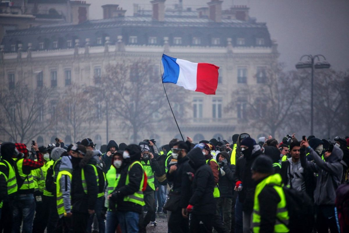 Demonstrators gather under a French flag near the Arc de Triomphe during a protest of Yellow Vests (Gilets jaunes) against rising oil prices and living costs in Paris on Dec 1, 2018,