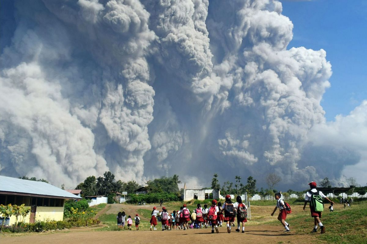 Schoolchildren walk together at Sipandak Elementary School in Tiga Pancur village in Karo, North Sumatra, on Feb 19, 2018, as thick ash from Mount Sinabung volcano rises into the air following an eruption.