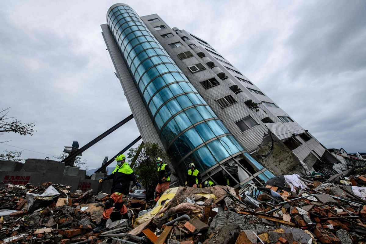 Rescue workers walk out from the Yun Tsui building, which is leaning at a precarious angle, in the Taiwanese city of Hualien on Feb 8, 2018, after the city was hit by a 6.4-magnitude quake late on Feb 6.