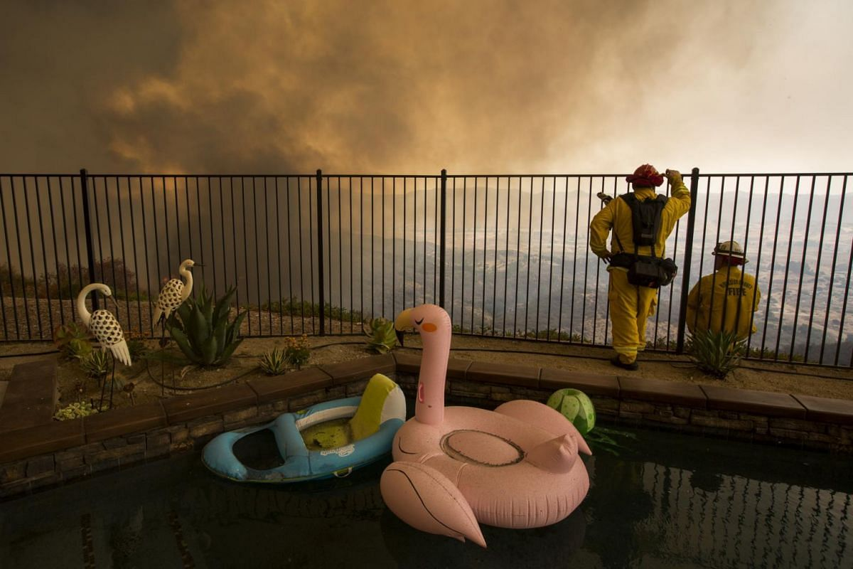 Firefighters near a backyard pool monitor flames threatening homes during the Holy Fire in Lake Elsinore, California, US, on Aug 9, 2018. A 51-year-old man has been arrested on arson charges that could lead to a life sentence for deliberately startin