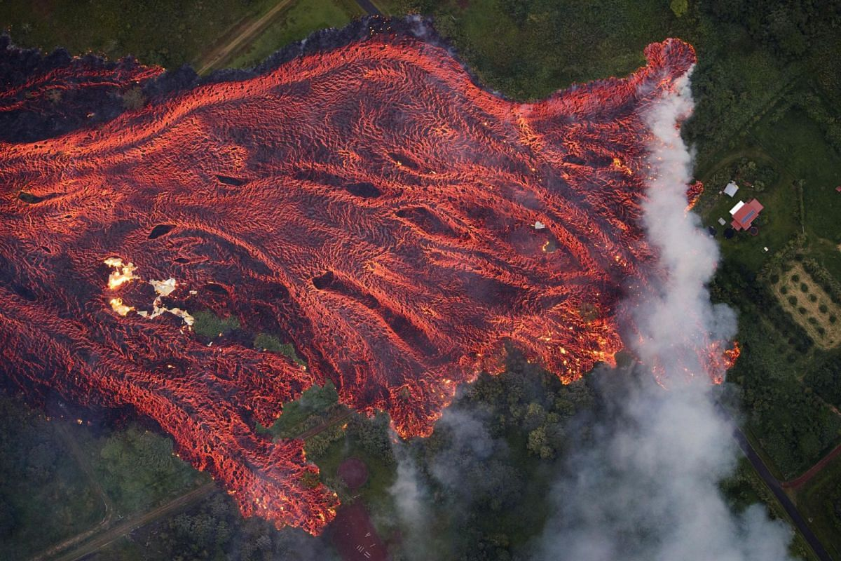 A massive fast-moving lava flow consumes everything in its path, with flames from the remnants of one home burning on the left, and another home on the right being threatened, in Pahoa, Hawaii, on May 19, 2018.