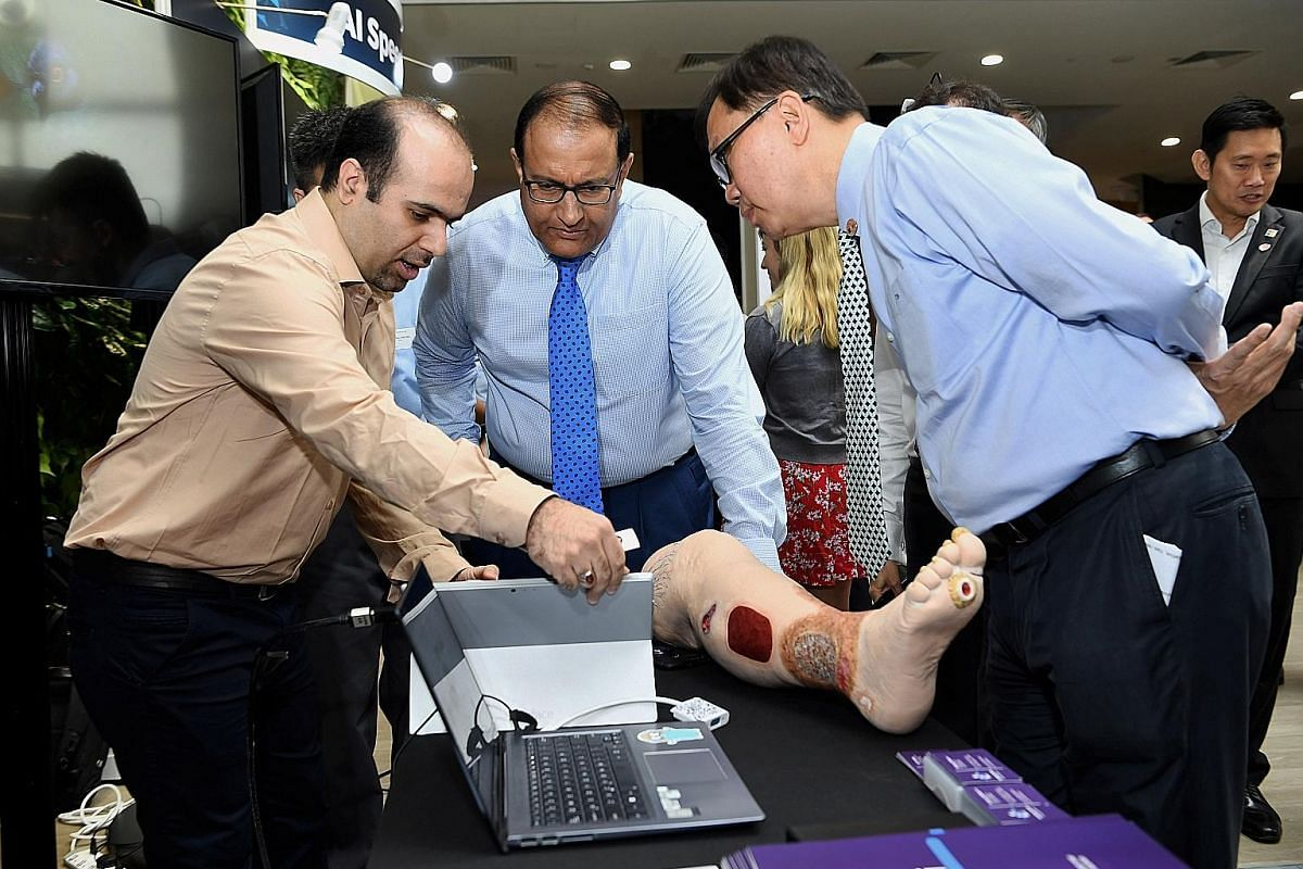 Minister for Communications and Information S. Iswaran (centre) observing a demonstration by KroniKare, which uses AI to assess wounds.