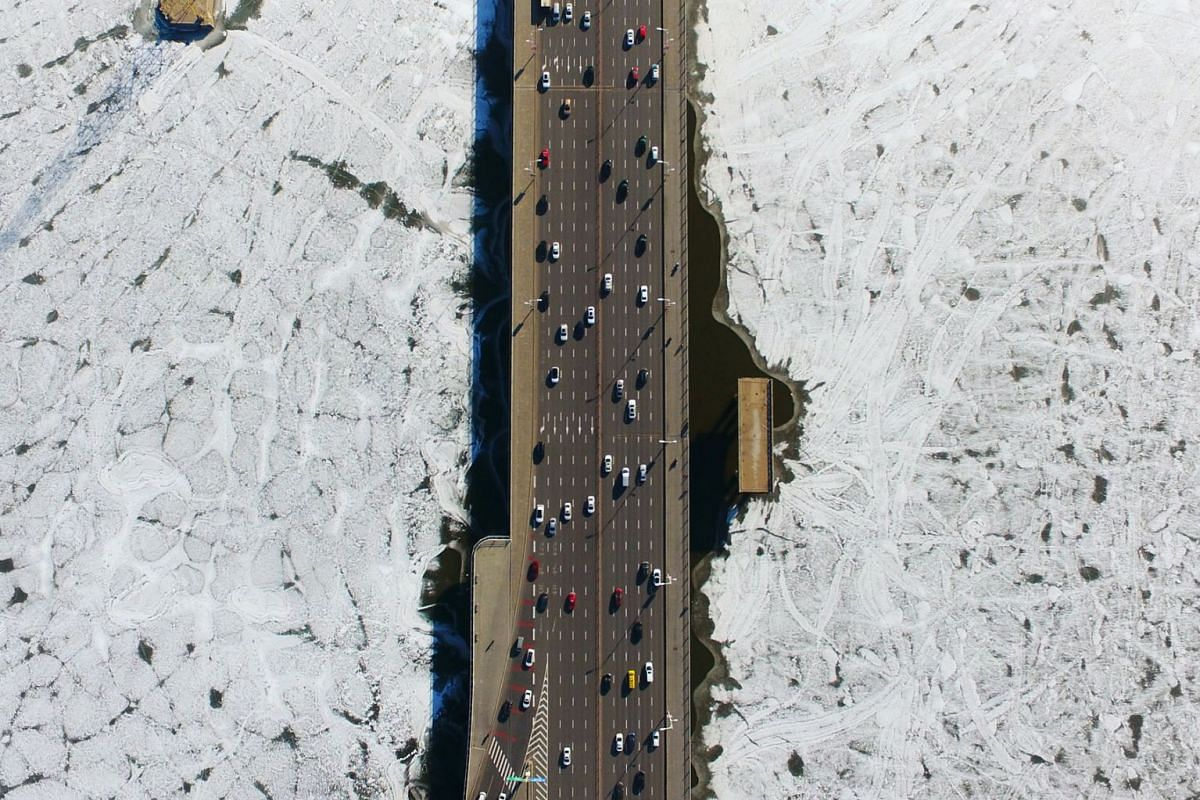 Vehicles travel on a bridge over the partially frozen Hun river in Shenyang, Liaoning province, China, December 25, 2018.