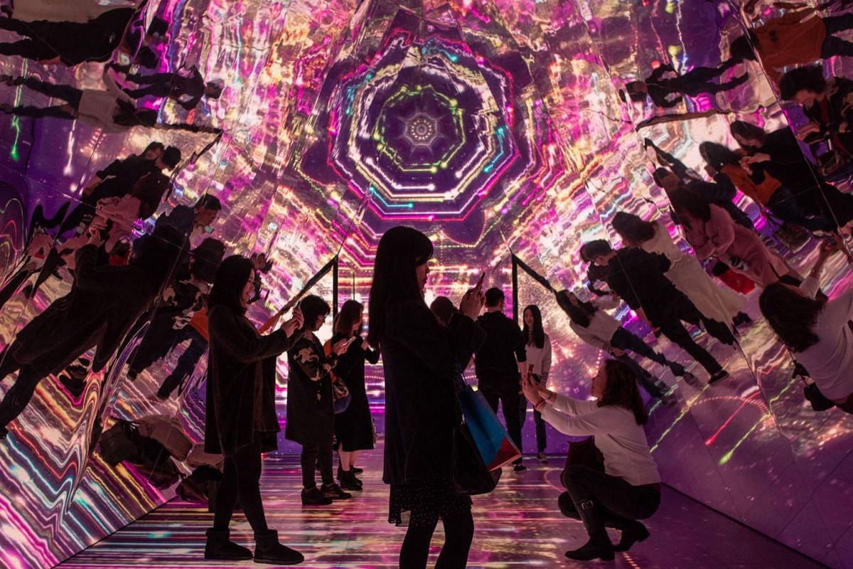 People stand inside a kaleidoscope installation, erected as part of Christmas festivities, at a shopping arcade in Hong Kong on December 25, 2018.