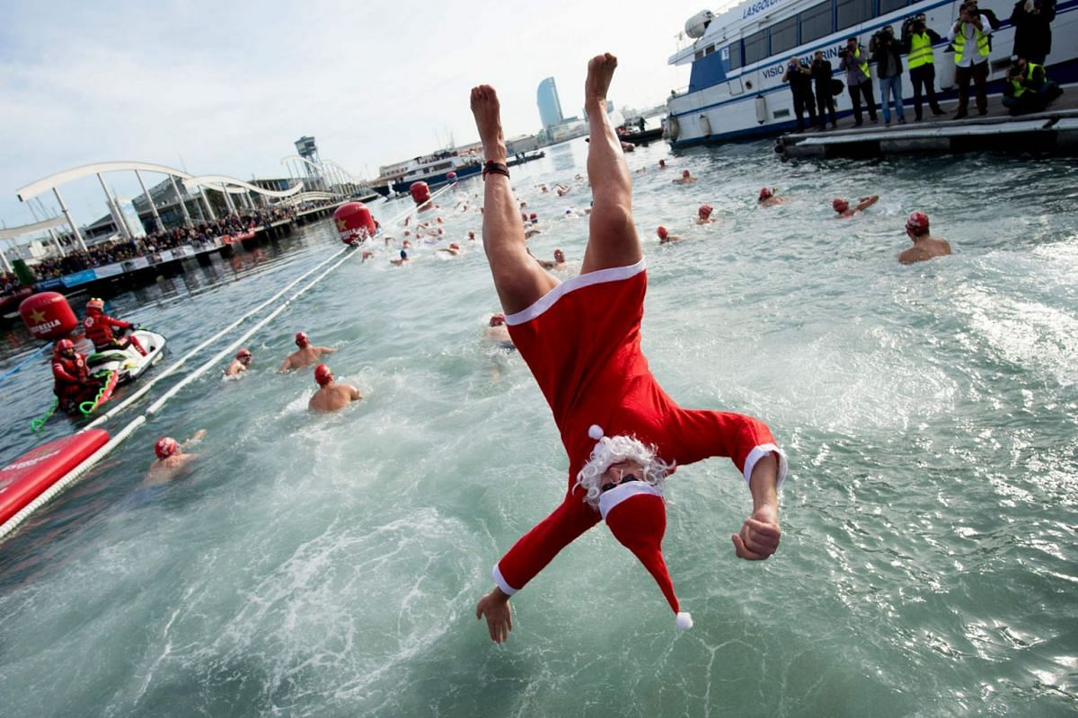 A participant in a Santa Claus costume jumps into the water during the 109th edition of the 'Copa Nadal' (Christmas Cup) swimming competition in Barcelona's Port Vell on December 25, 2018. The traditional 200-meter Christmas swimming race gathered mo