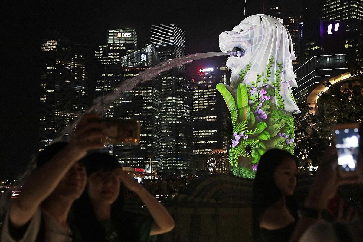 Left: The Merlion illuminated by an animated light projection during a test last Friday. As part of the Marina Bay countdown celebrations, the Merlion and other landmarks will feature such projections - adapted from artworks created by Nanyang Academ