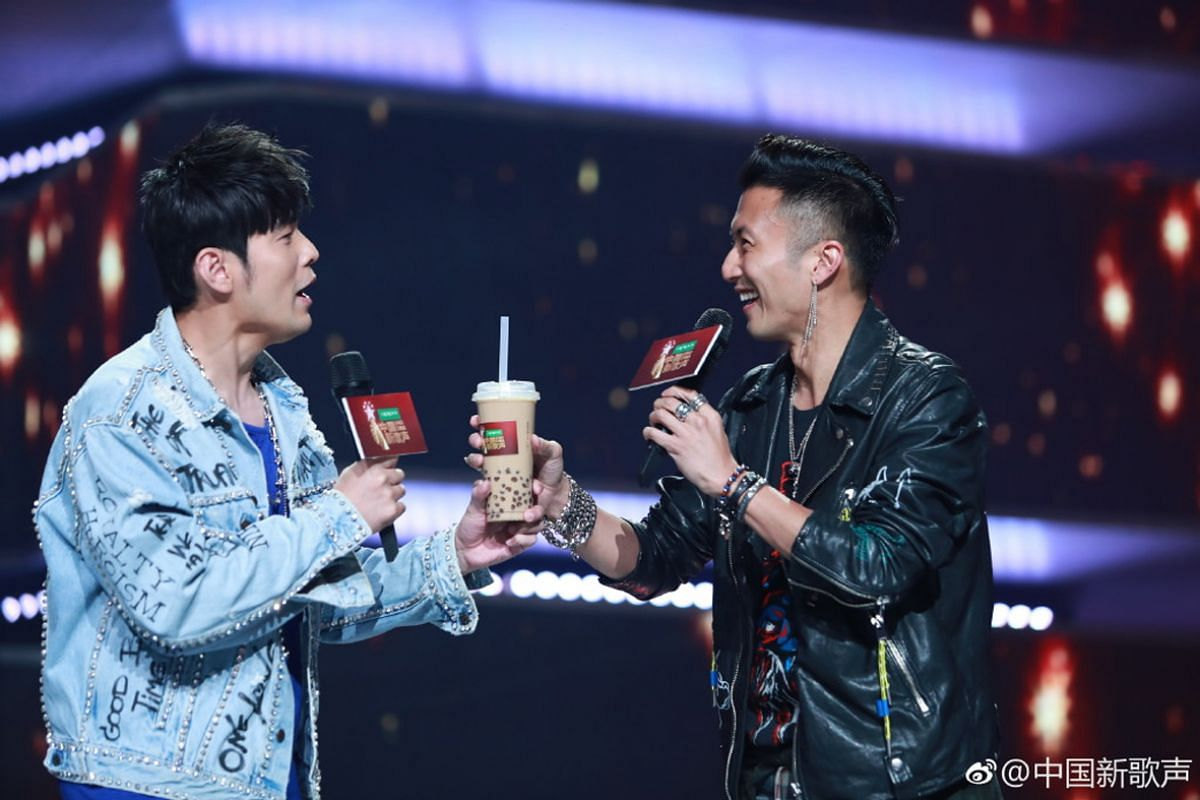 Hong Kong entertainer Nicholas Tse (right) offering Taiwanese singer Jay Chou a cup of bubble tea during a television variety show.