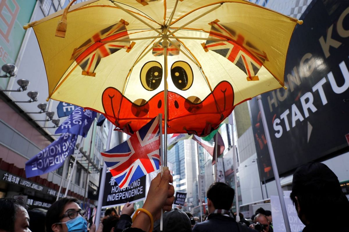 A pro-independence supporter raises an umbrella with British flags as she takes part in an annual New Year's Day march in Hong Kong, China January 1, 2019. PHOTO: REUTERS