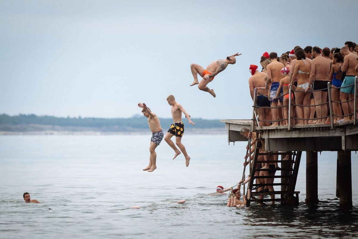 People swim and jump into the water during a traditional New Year's swim in the Adriatic sea in Portoroz, Slovenia on January 1, 2019. PHOTO: AFP