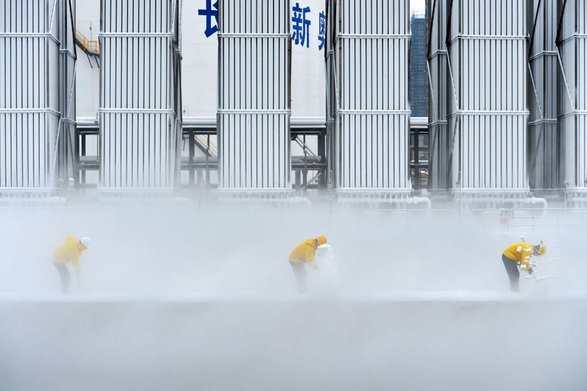 Workers remove snow at a liquefied natural gas (LNG) facility of ENN Group in Changsha, Hunan province, China December 31, 2018. PHOTO: REUTERS