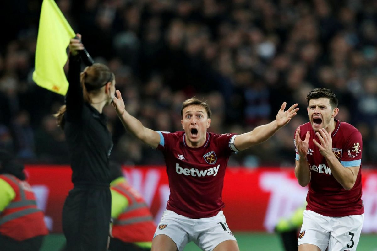 West Ham's Mark Noble and Aaron Cresswell protest with a match official during the Premier League football match between West Ham United and Brighton & Hove Albion at the London Stadium in London, Britain on January 2, 2019. PHOTOH: REUTERS