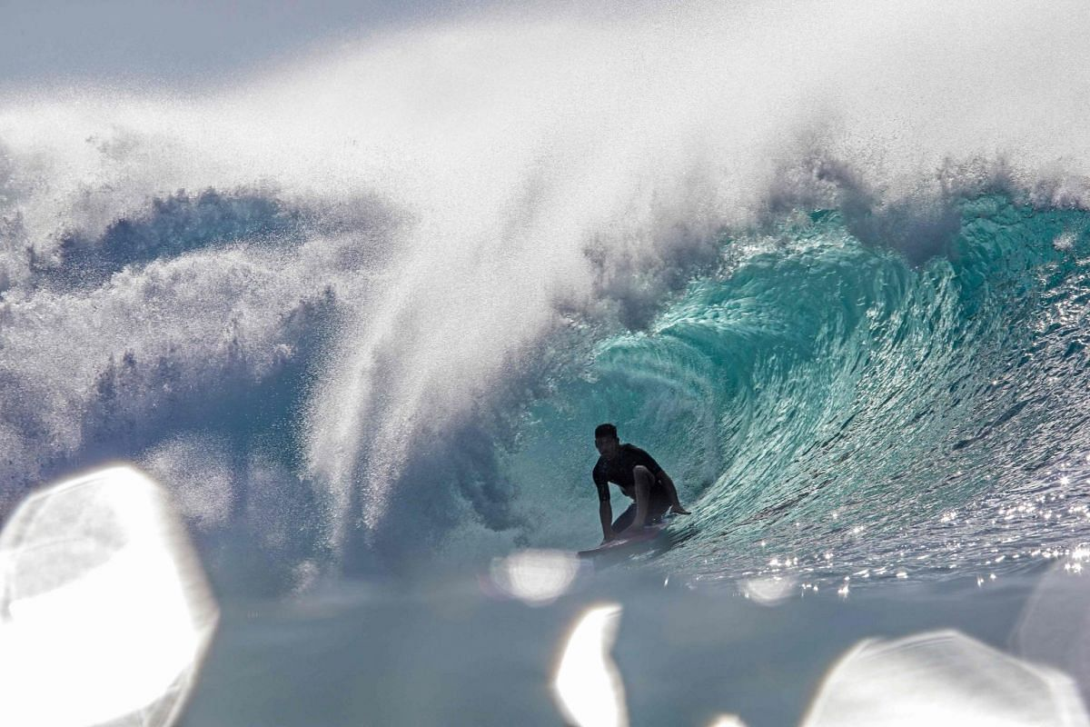 A surfer rides a wave while practicing for Da Hui Backdoor shootout at the Pipeline Masters on Oahu's North Shore, Hawaii on January 2, 2019. PHOTO: BRIAN BIELMANN PHOTOGRAPHY VIA AFP