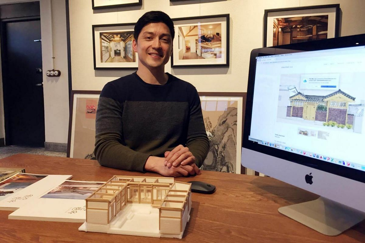 German-Korean architect Daniel Taendler, a hanok specialist, posing in his office with a drawing of a hanok that he will be rebuilding for a client.