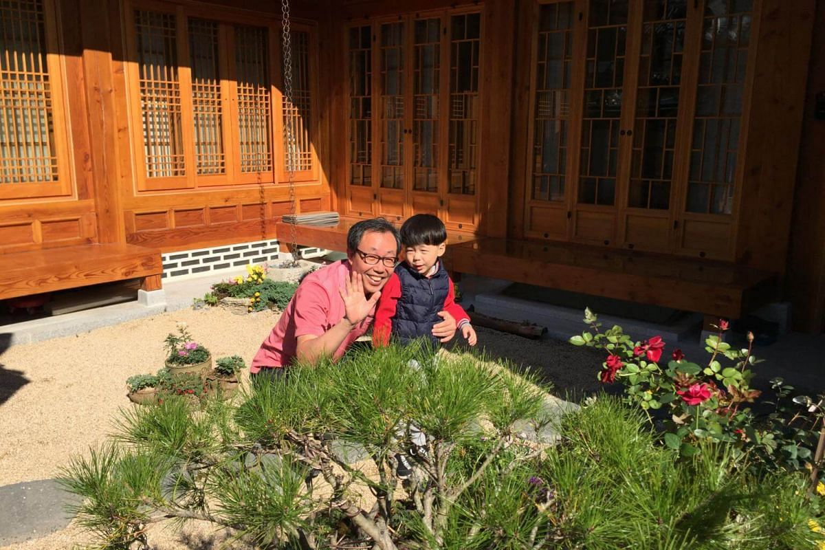 Retiree Kim Sun-dae with his 4-year-old grandson in the couryard of his hanok.