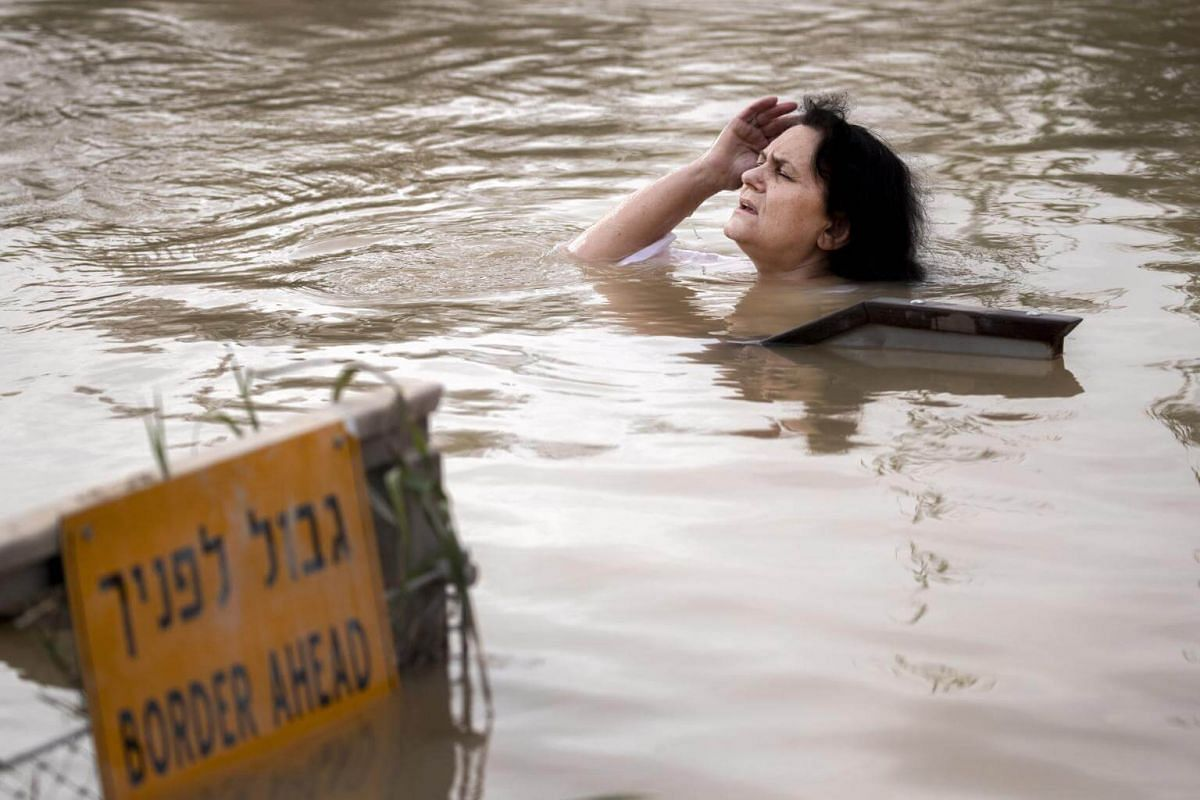 A Greek Orthodox Christian woman chants prayers as she emerges from the Jordan River at the baptism site at Qasr el Yahud near Jericho in the West Bank, on Jan 6, 2019.