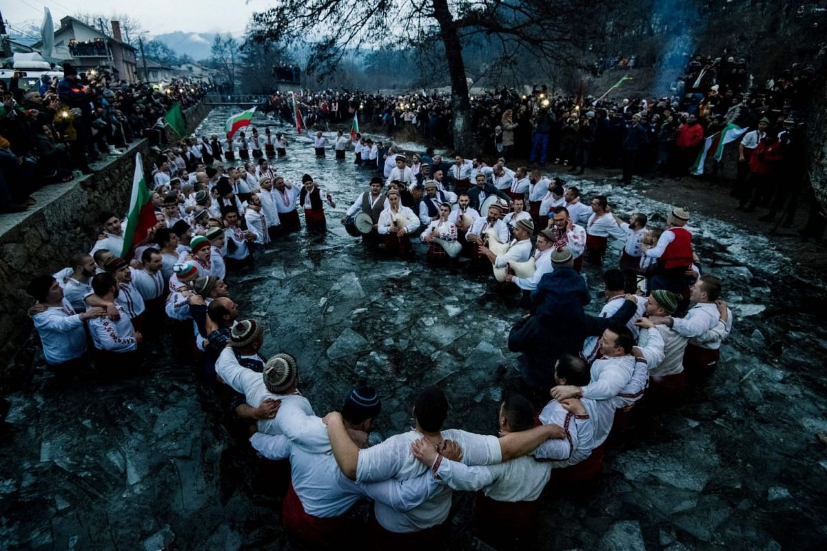 """Bulgarian men perform the traditional """"Horo"""" dance in the icy winter waters of the Tundzha river in the town of Kalofer, as part of Epiphany Day celebrations on January 6, 2019. PHOTO: AFP"""