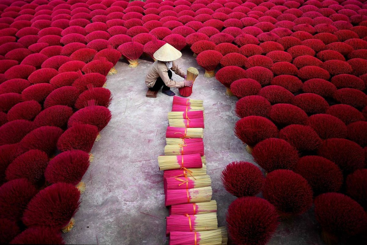 A photo released on January 8, 2019, shows shows a Vietnamese woman collecting incense sticks in a courtyard in the village of Quang Phu Cau on the outskirts of Hanoi on January 3, 2019. PHOTO: AFP