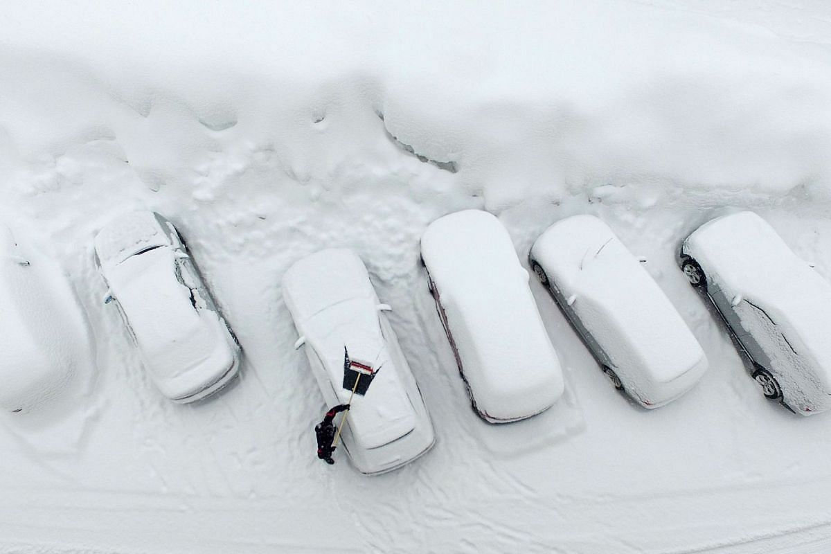 An aerial picture taken on January 8, 2019 shows a man clearing his car from the snow after heavy snowfalls in Ramsau am Dachstein, Austria. PHOTO: AFP