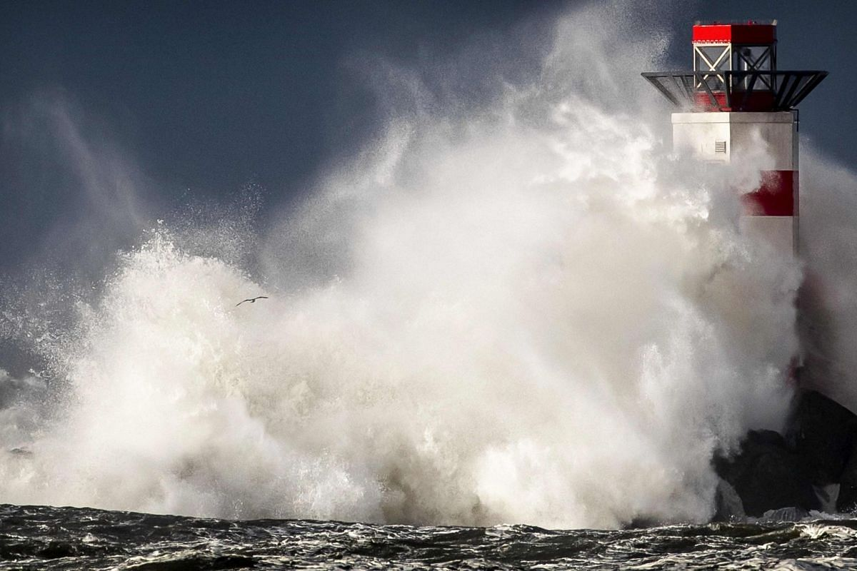 Large waves hit the lighthouse of IJmuiden on The Netherlands' North Sea coast during the first storm of the year on January 8, 2019. PHOTO: AFP