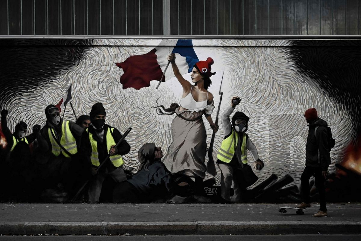 """A man with a skateboard passes by a mural by street artist PBOY depicting gilets jaunes inspired by """"La Liberte guidant le Peuple"""" painting in Paris on January 8, 2019. PHOTO: AFP"""