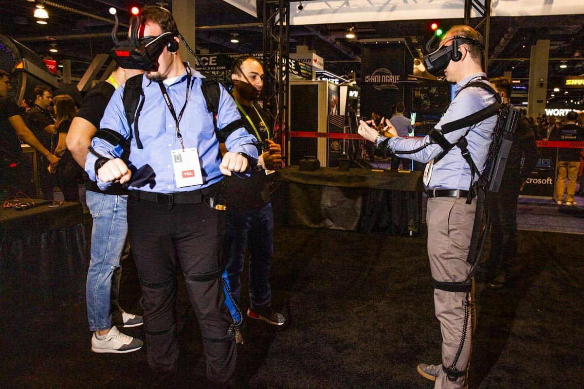 Attendees try full body hyperreality sensors at the 2019 Consumer Electronics Show.