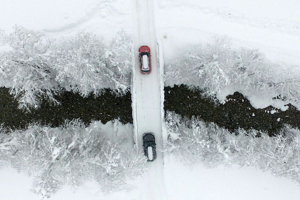 An aerial view shows cars crossing a bridge as the street is snow covered on January 9, 2019 in Untertauern, Austria. PHOTO: AFP