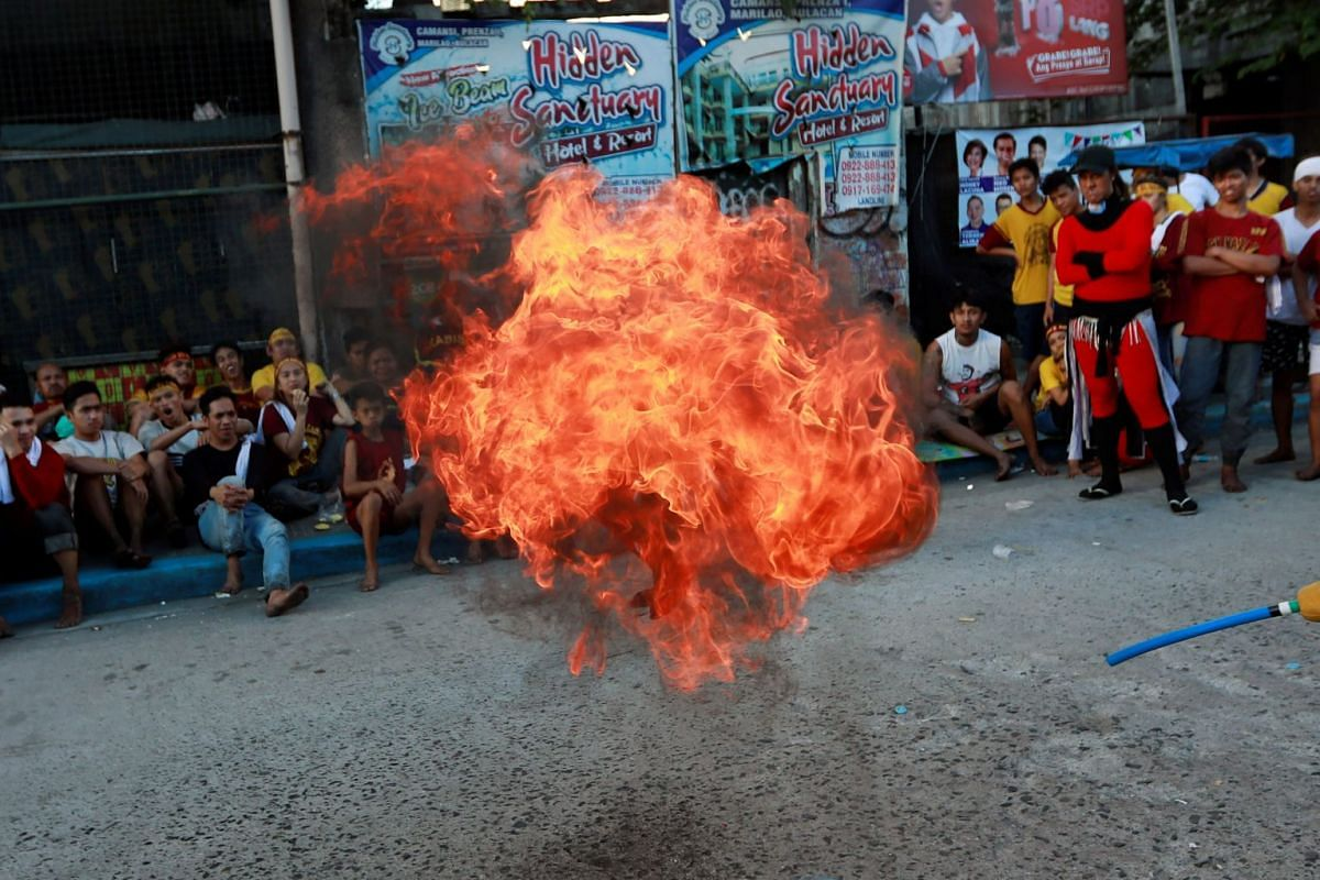 A firebreather performs as Catholic devotees celebrate and wait to touch the statue of the Black Nazarene on its feast day in Manila, Philippines, January 9, 2019. PHOTO: REUTERS