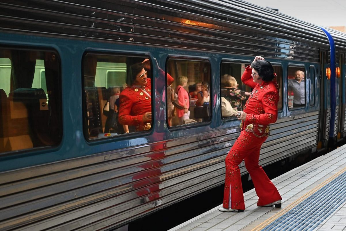 An Elvis impersonator uses a train window as a mirror at Central station before boarding a train to the Parkes Elvis Festival.