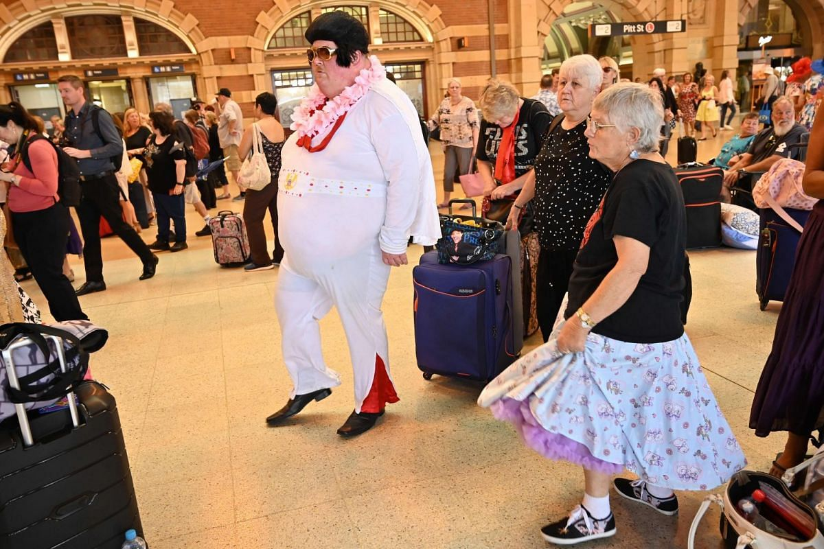 An Elvis impersonator and a fan dancing to Elvis songs at Central station in Sydney.
