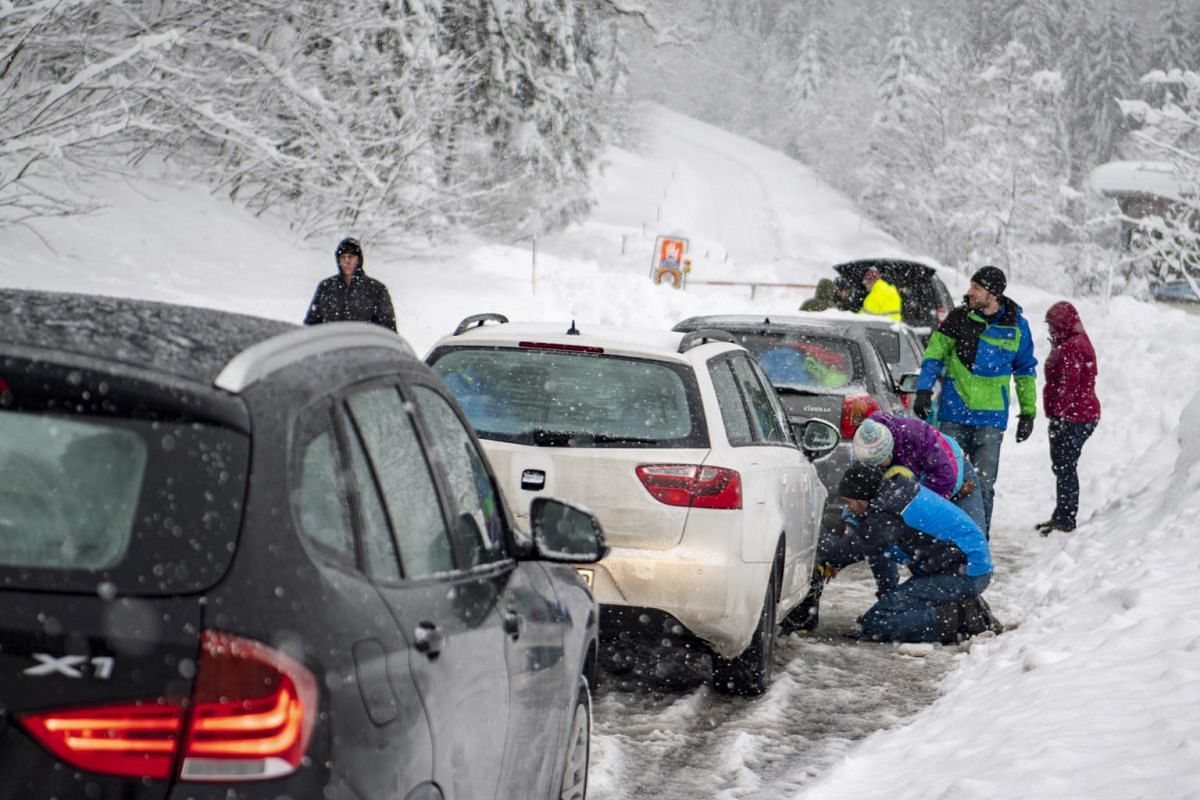 """People put snow chains on their car tyres in front of a closed road during heavy snowfall. A multi-language sign warns of the """"danger of avalanches"""" near Untertauern, Austria."""