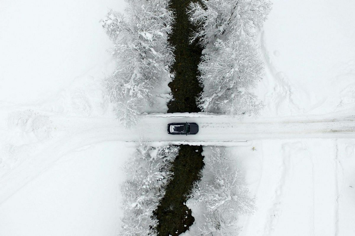 An aerial view of a car crossing a bridge as the surrounding landscape is covered in snow, in Untertauern, Austria.