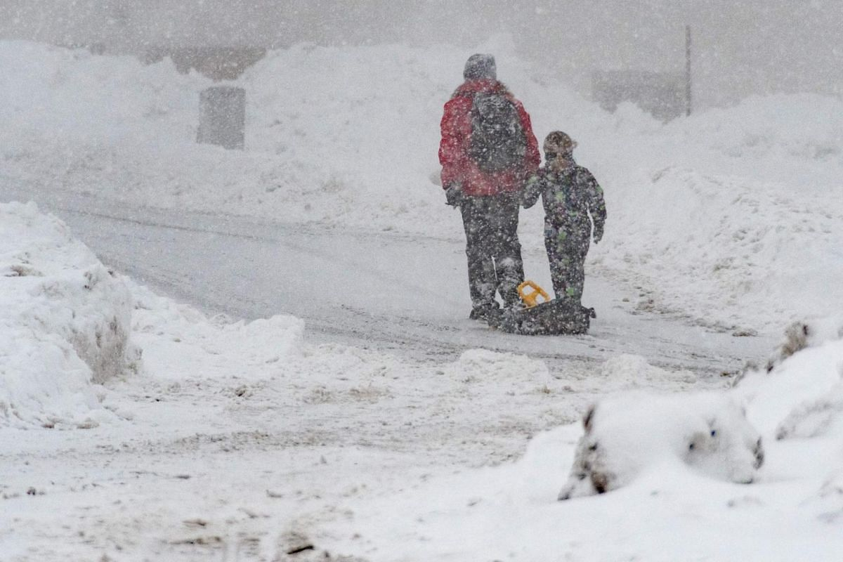 A woman and a child with a sledge walk through a snowy street in Sankt Englmar, southern Germany.