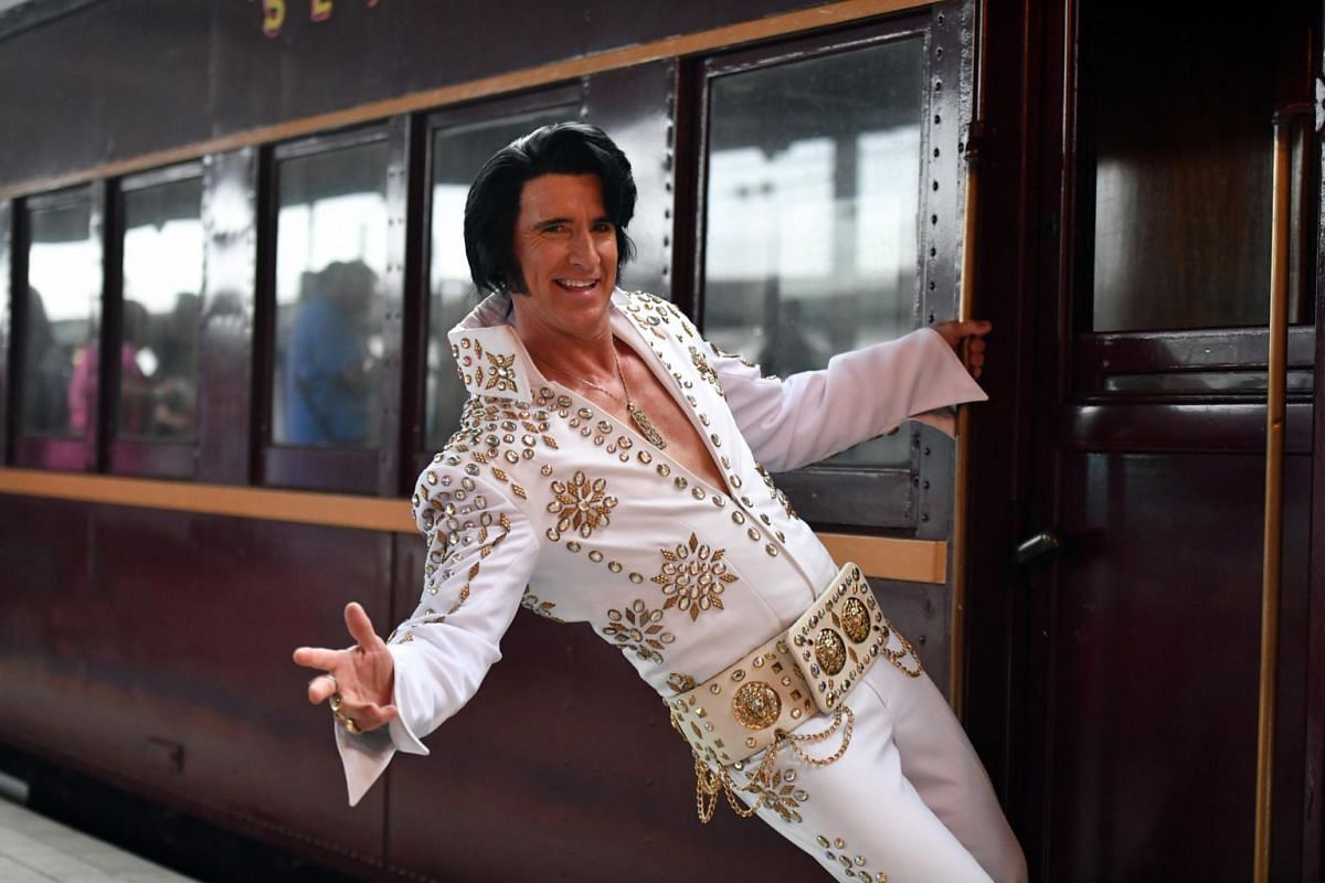 """Elvis impersonator Kingsley Rock posing for a photograph before boarding the """"Elvis Express"""" at Central station in Sydney on Jan 10, 2019."""