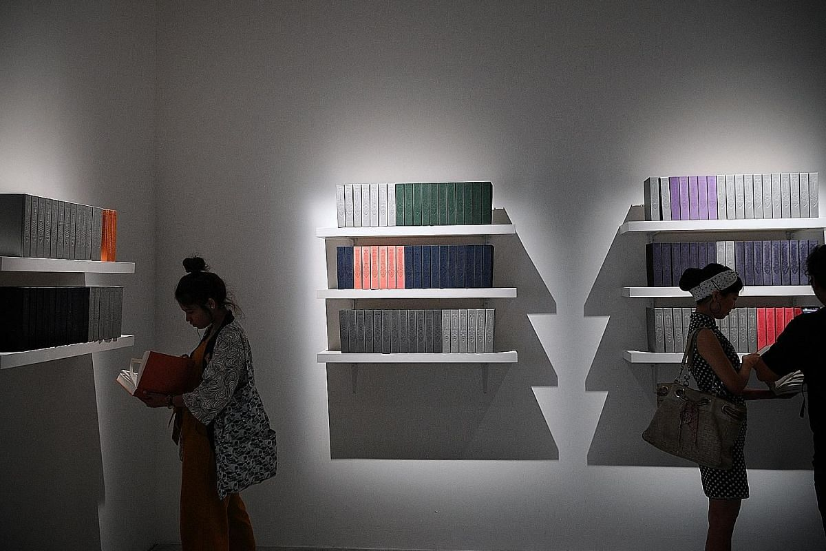 APB Foundation Signature Art Prize Jurors' Choice Award recipient Shubigi Rao (left) and Hollywood actress and artist Lucy Liu at their joint exhibition, Unhomed Belongings, at the National Museum of Singapore. These shelves hold handmade books from