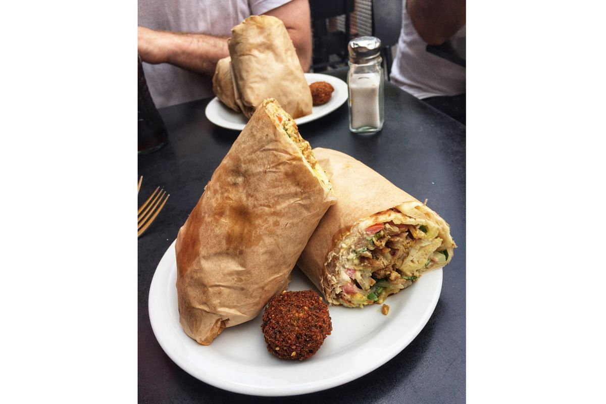 Shawarma (thin slices of marinated meat stacked and cooked in a rotisserie) wrapped in pillowy flatbread called lafa