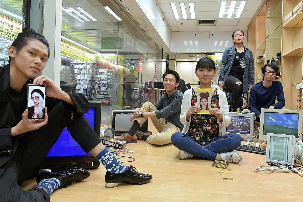 Artist assistant Jovan Tng (far left) holds up an image of Singaporean artist Chong Weixin, who is participating virtually in the Sim Lim Square Art Residency by art collective Inter-Mission. Also taking part are (from left) Singaporean artist Johann