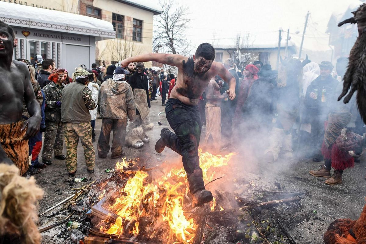 A reveler jumps over an open fire during the traditional mask burning on the second day of a carnival procession through the village of Vevcani, on Jan 14, 2019. The Vevcani Carnival is said to be 1.400 years old and is held every year on the eve of
