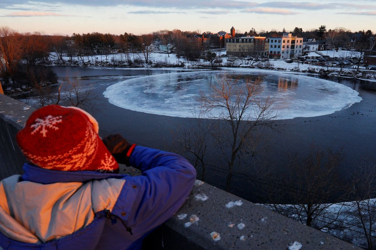 An onlooker watches a large, circular ice floe in the Presumpscot River in Westbrook, Maine, U.S., Jan 16, 2019.