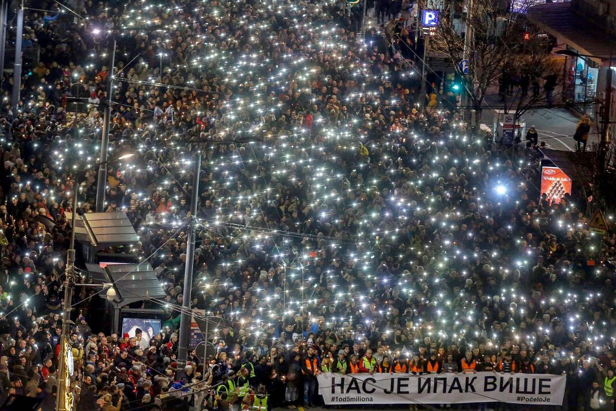 Anti-government protesters hold up their phones and candles and hold a banner in Cyrillic writing that reads 'Still there is more of us' as they arrive at the end of their silent march in memory of Serb politician Oliver Ivanovic in Belgrade on Jan 1