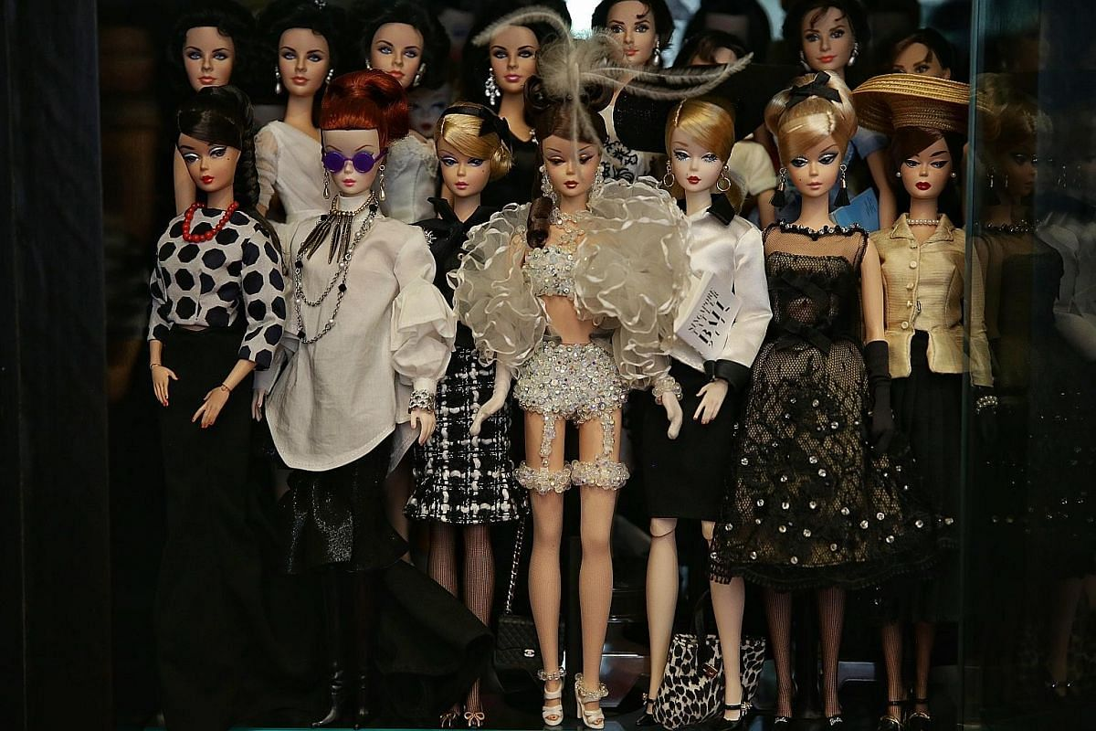 The most expensive Barbie in Mr Yang's collection is a Silkstone doll decked in Swarovski crystals. He paid $3,600 for it at a charity auction in 2000. Mr Yang takes a selfie with a Ken doll customised to look like him. Four Barbie mermaid dolls on t