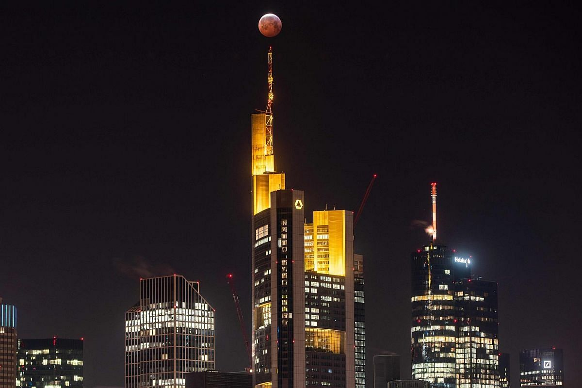 A Super Blood Moon is seen above the Frankfurt skyline during a lunar eclipse on Jan 21, 2019.