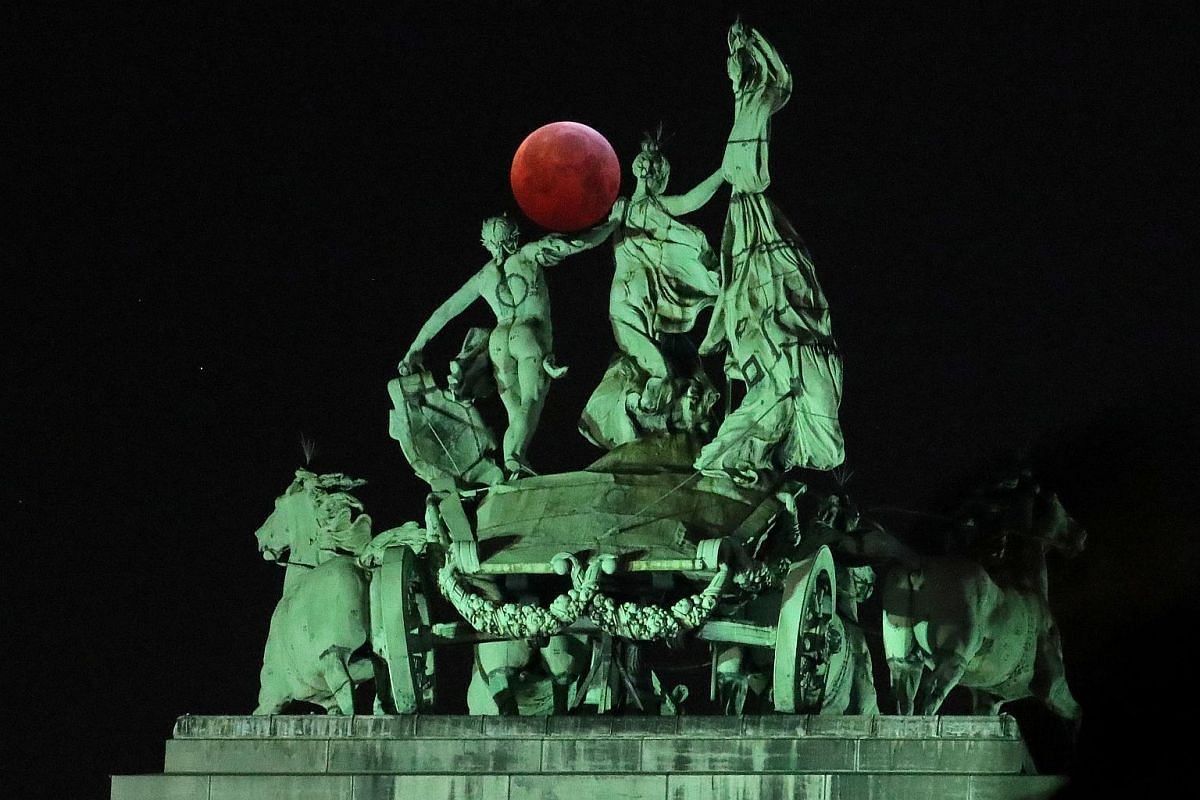 The moon is seen beside a quadriga on the top of the Cinquantenaire arch during a total lunar eclipse, known as the Super Blood Wolf Moon, in Brussels, Belgium on Jan 21, 2019.