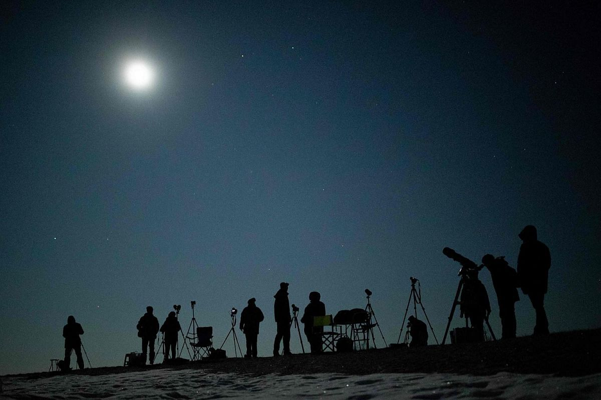 People gather as they wait for the appearance of a Blood Moon total lunar eclipse over Vienna on Jan 21, 2019.
