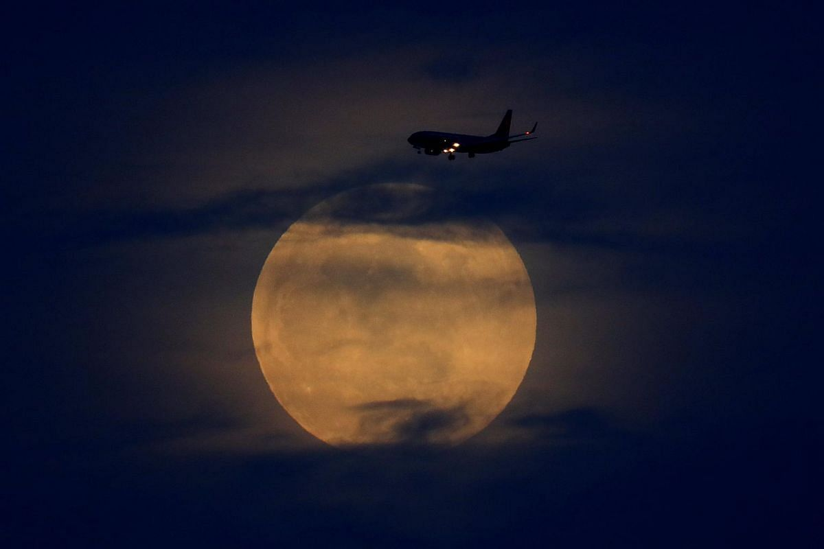 A full moon rises between clouds as a landing commercial jet approaches the airport before the start of a total lunar eclipse that is being called a Super Blood Wolf Moon in San Diego, California, on Jan 20, 2019.