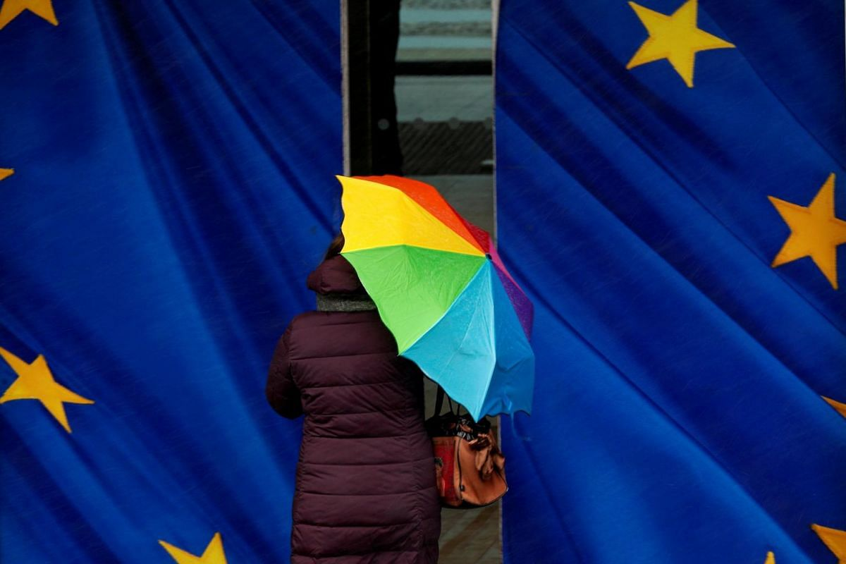 A woman holds an umbrella as she enters the European Commission headquarters in Brussels, Belgium, on Jan 22, 2019.
