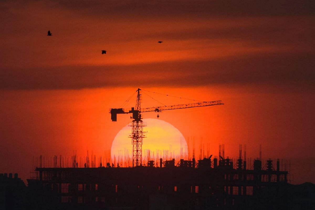 Labourers work at a building construction site during a sunset in Yangon, Myanmar, on Jan 22, 2019.