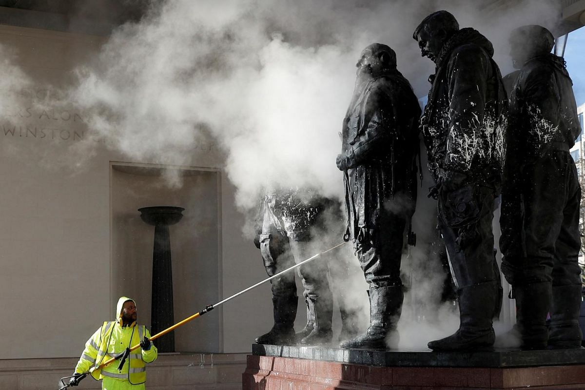 A worker cleans the paint-defaced Bomber Command Memorial in Green Park, London, Britain, on Jan 22, 2019.