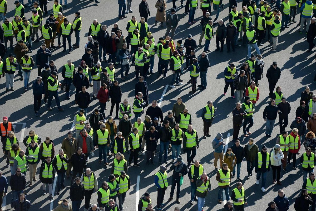 Spanish taxi drivers, many wearing yellow vests like protesters against the government in neighbouring France, march during a strike in Barcelona to protest against regulations proposed by the authorities for Tourism Vehicles with Chauffeur on Jan 22