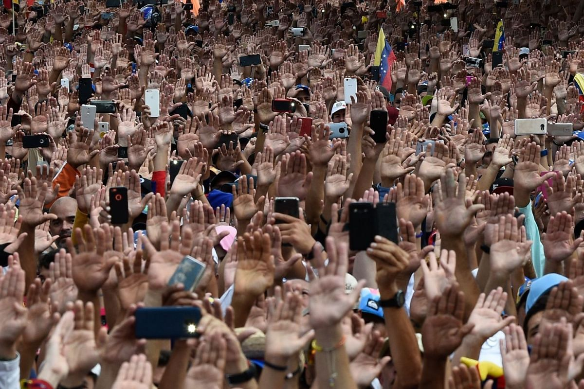 """People raise their hands during a mass opposition rally against Venezuelan President Nicolas Maduro, in which National Assembly head Juan Guaido (out of frame) declared himself the country's """"acting president"""", on the anniversary of a 1958 uprising t"""